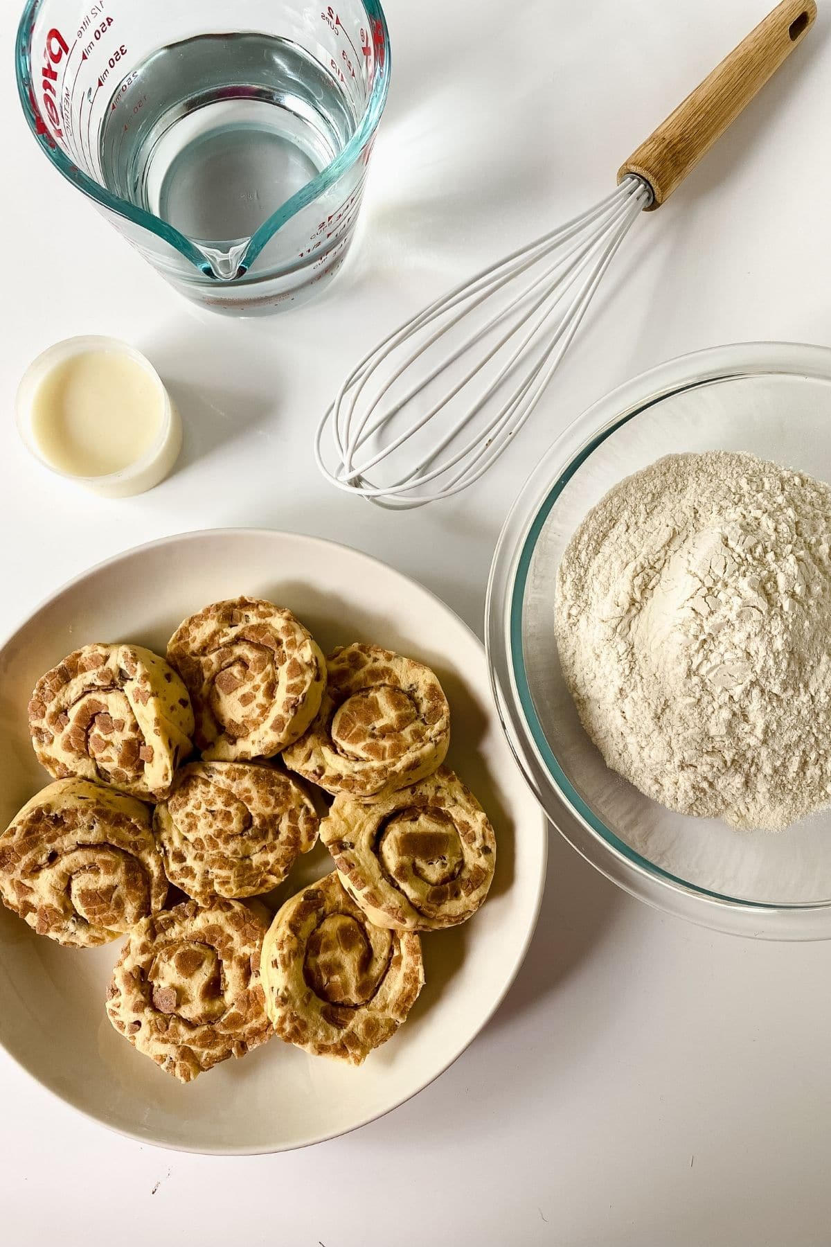 white plate of raw cinnamon rolls next to bowl of flour
