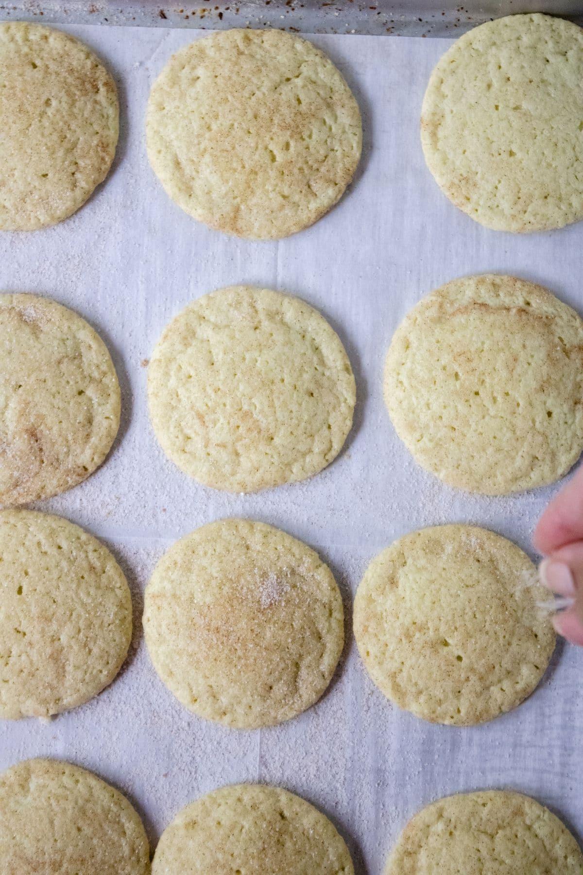 hand sprinkling sugar onto cookies