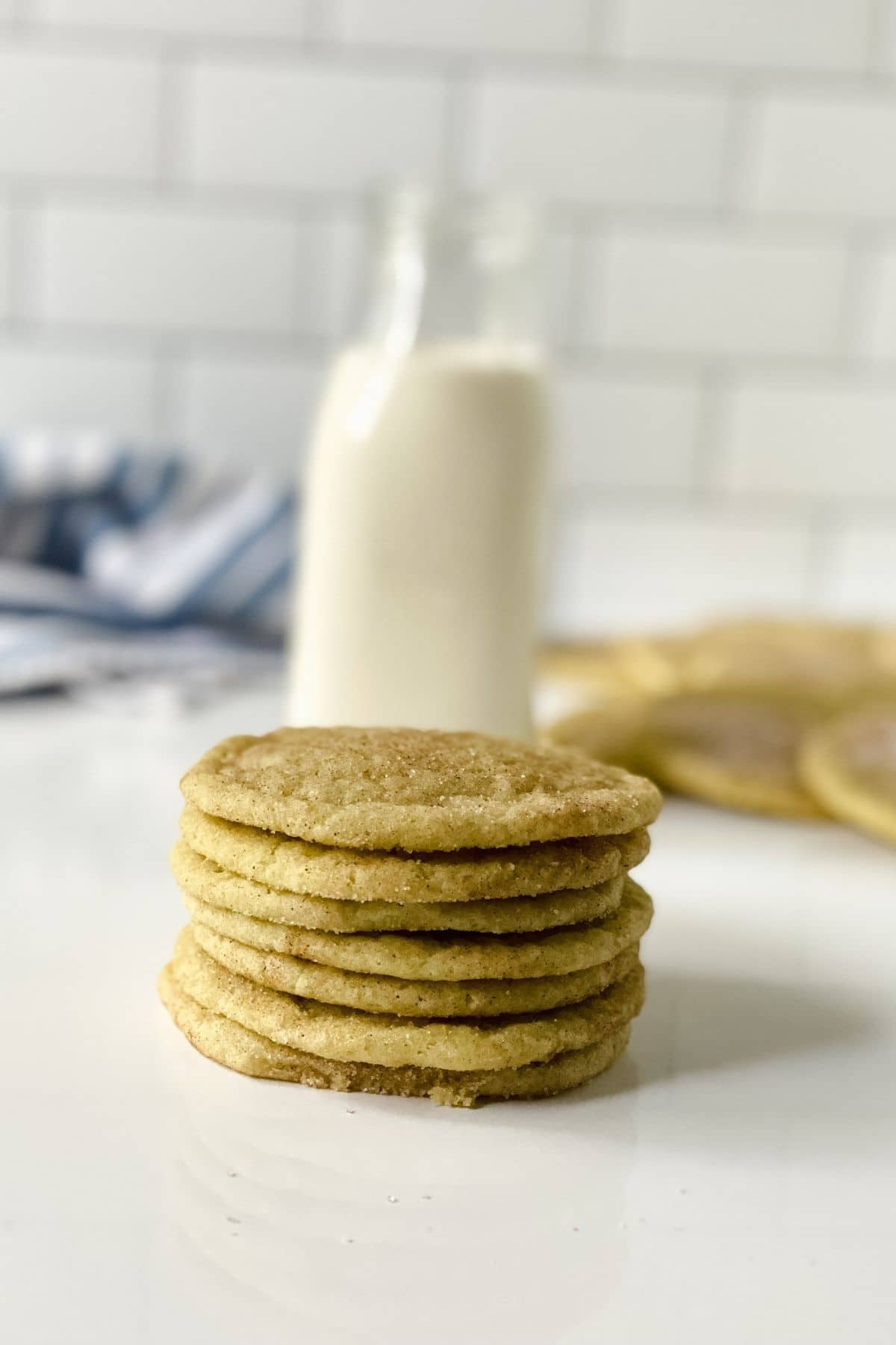 stack of cookies on white table in front of bottle of milk