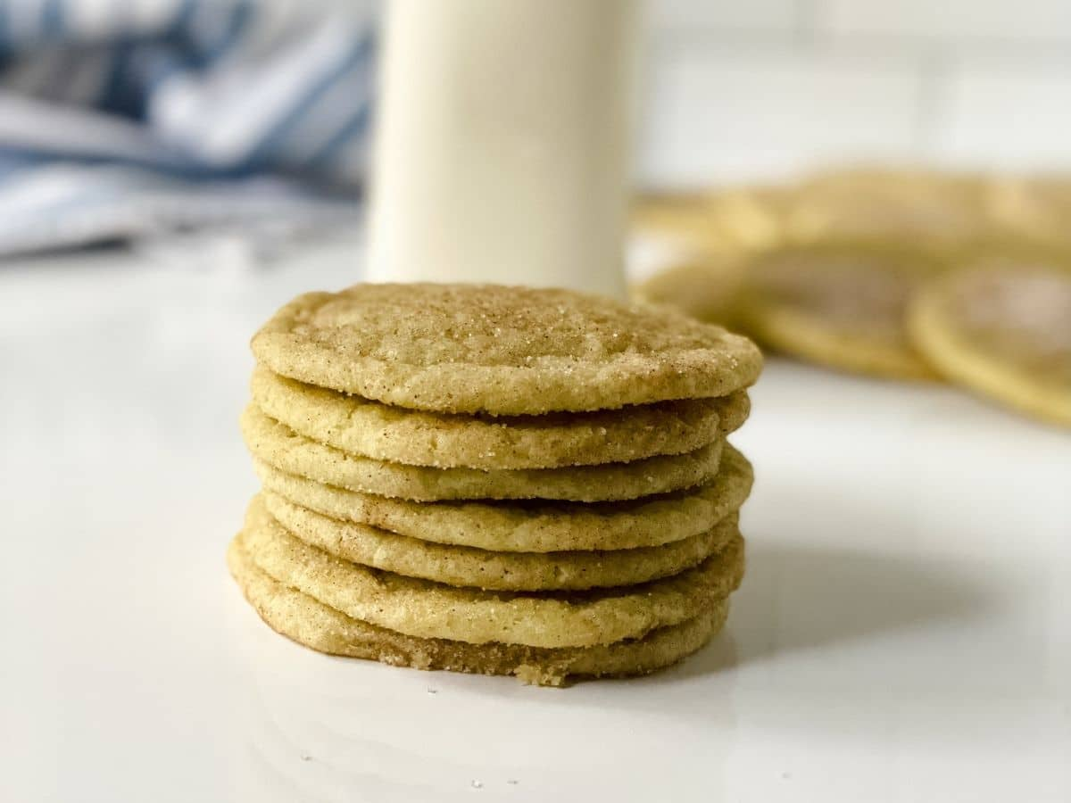 short stack of cookies on table by glass bottle of milk