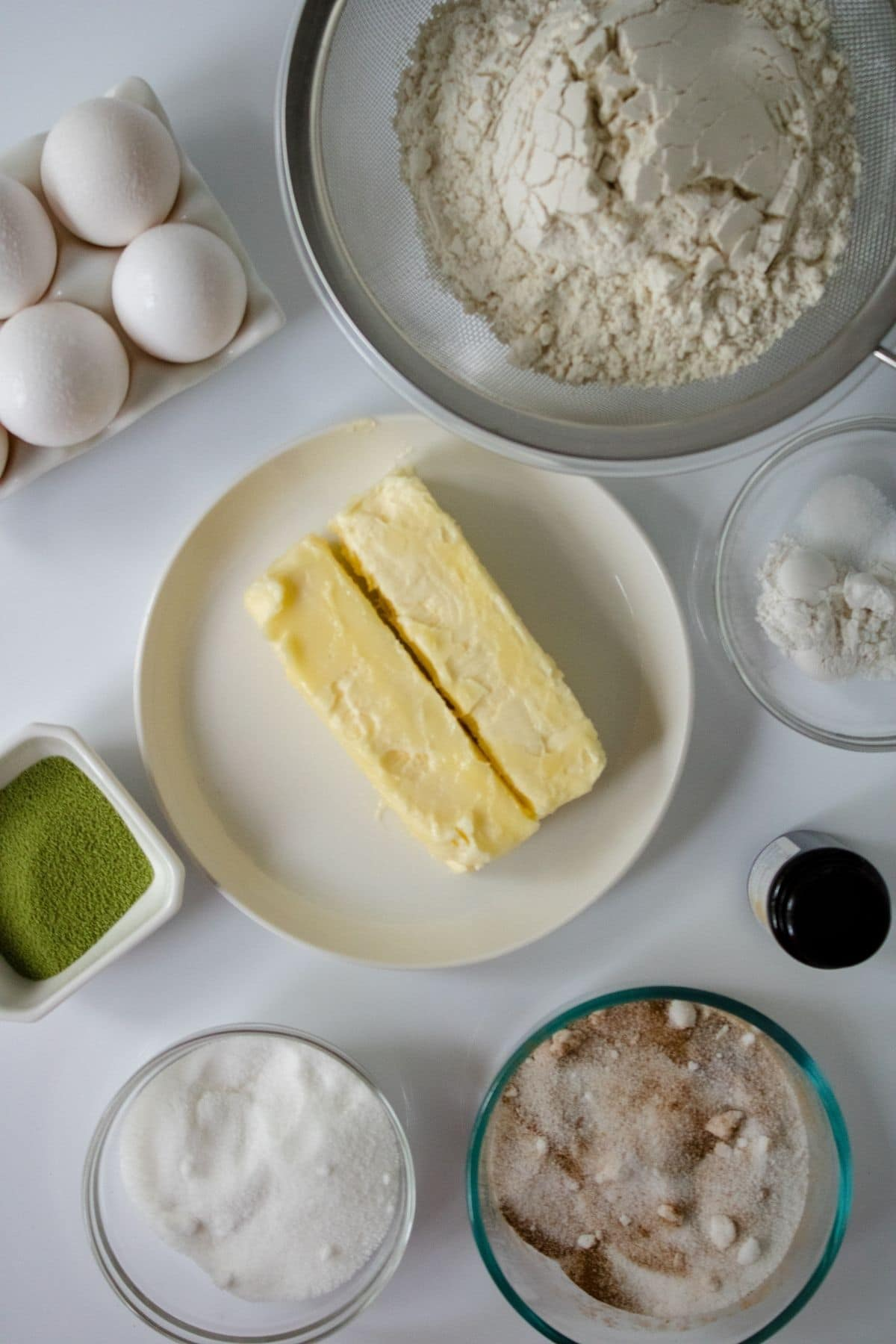 white plate of butter in center of white table surrounded y glass bowls of flour and sugar