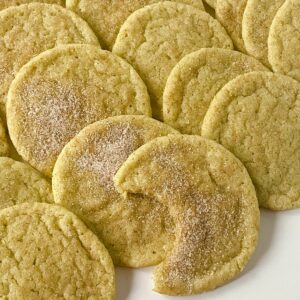 stack of snickerdoodles on table with one half eaten in front