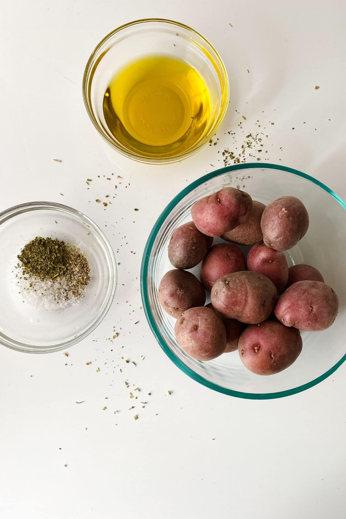 glass bowls of oil herbs and potatoes on white table