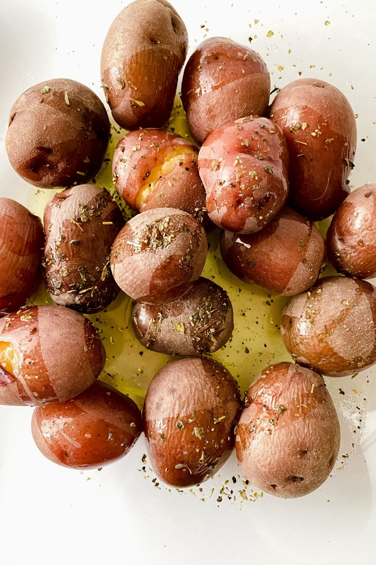 boiled red potatoes in bowl with olive oil and herbs